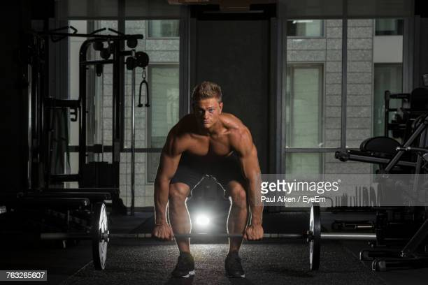 Portrait Of Young Man Exercising With Barbells At Gym