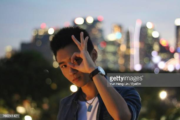 Portrait Of Young Man Gesturing Against City Lights At Night