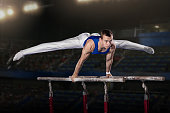 portrait of young man gymnasts competing in the stadium