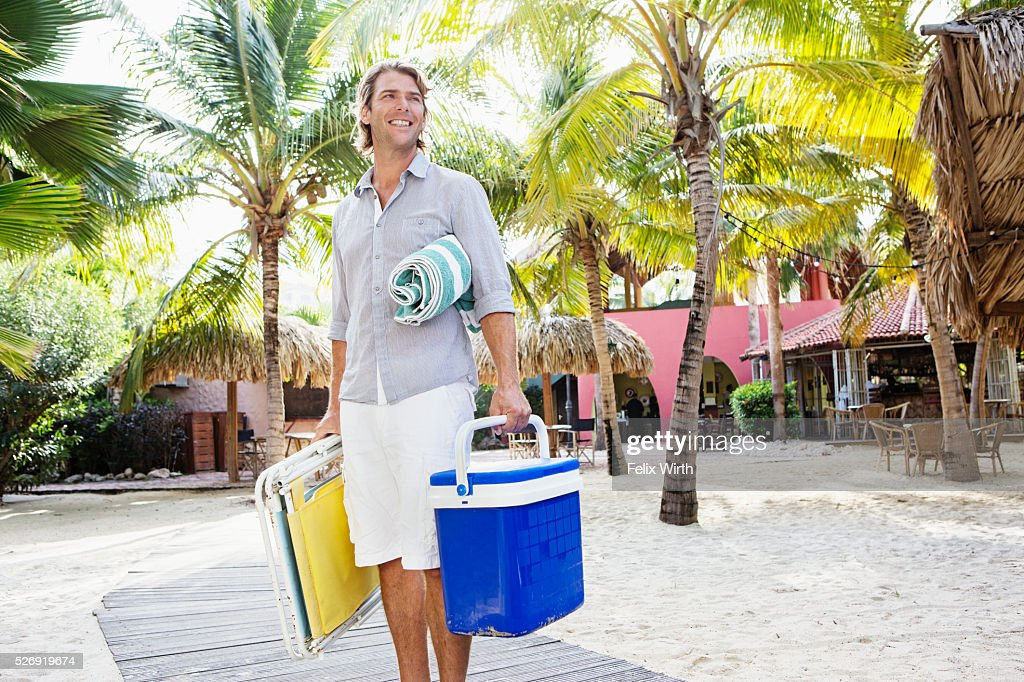Portrait of young man holding beach equipment : Stockfoto
