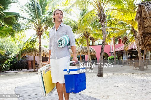 Portrait of young man holding beach equipment : Foto de stock