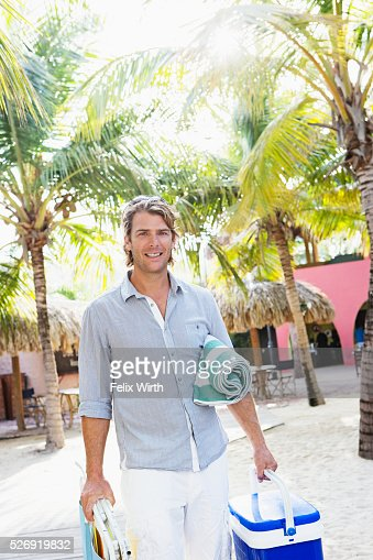 Portrait of young man holding beach equipment : Foto stock
