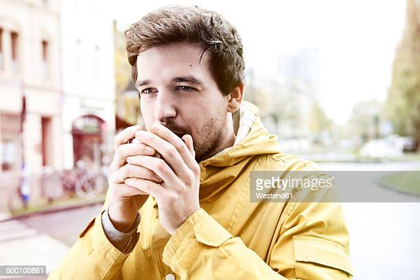 Portrait of young man holding coffee cup