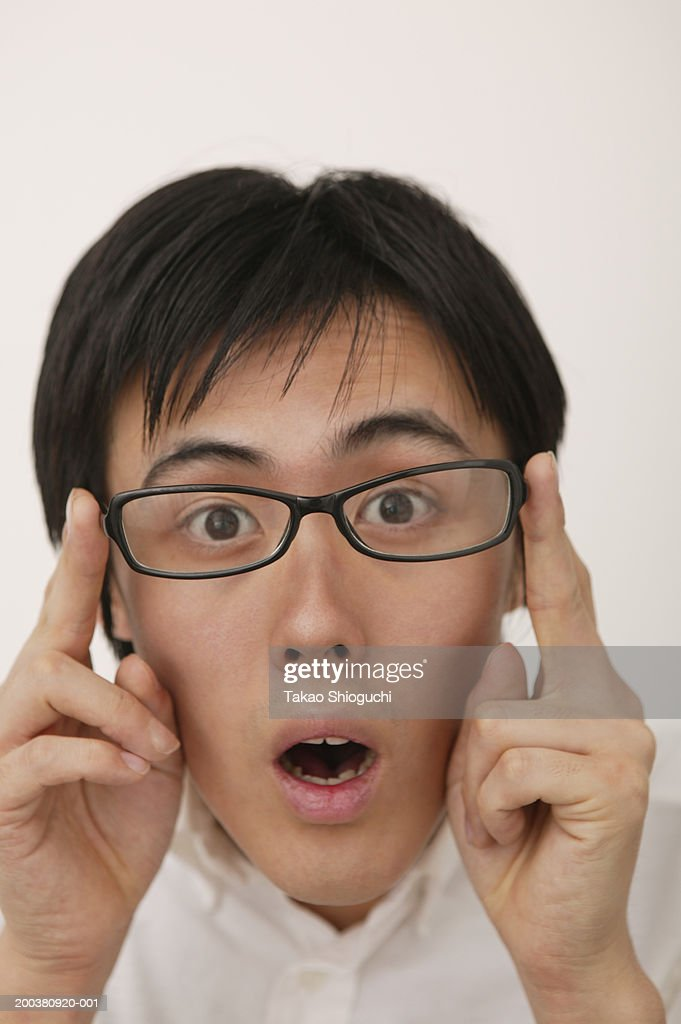 Portrait of young man holding glasses, mouth open : Stock Photo
