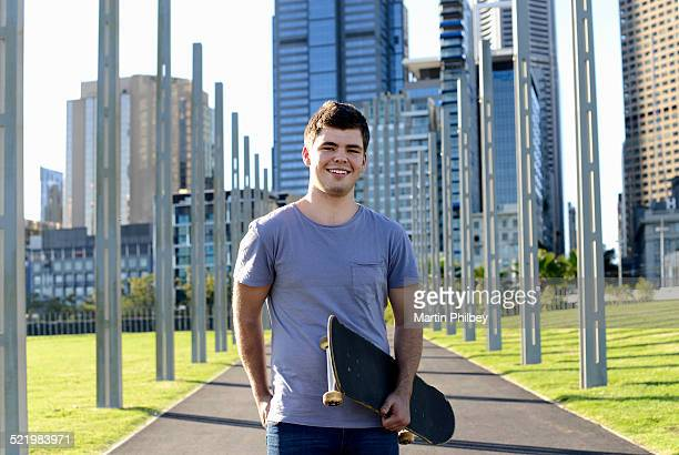 Portrait of young man holding skateboard