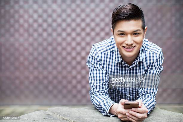 Portrait of young man holding smartphone