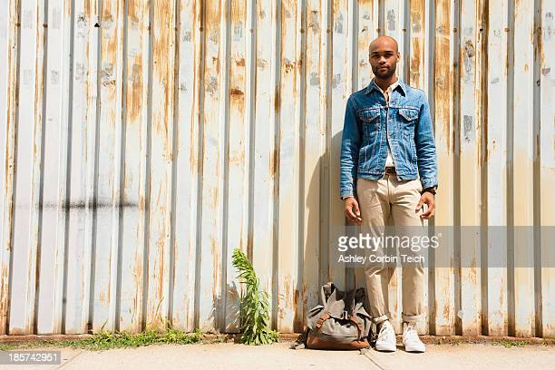 Portrait of young man in front of corrugated fence