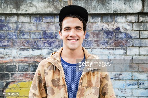 Portrait of young man in front of graffiti wall