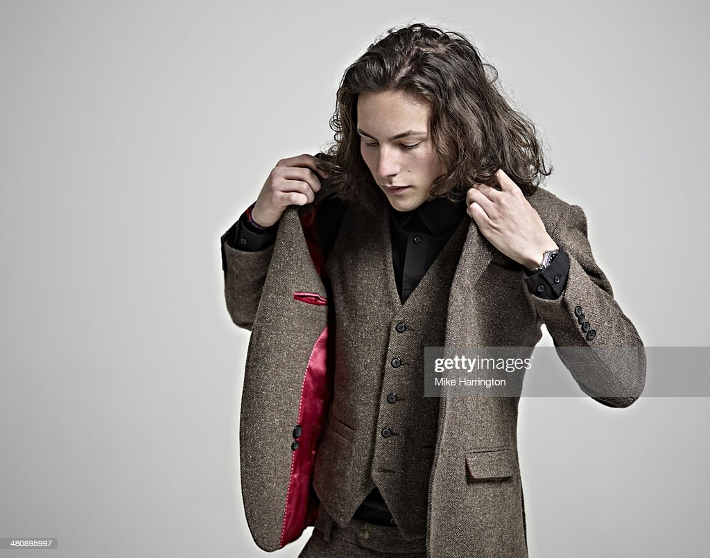 Portrait of young man in suit putting on jacket.