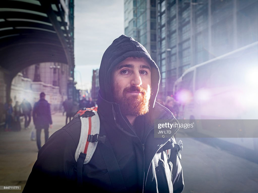 Portrait of young man, in urban street
