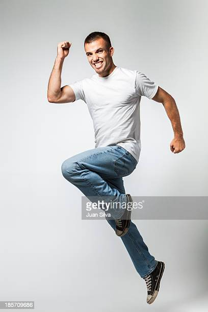 Portrait of young man jumping with big smile