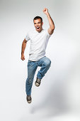 Portrait of young man jumping with mouth wide open