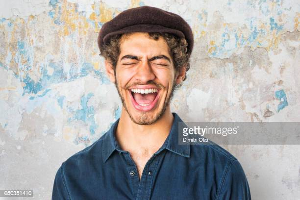 Portrait of young man laughing, eyes closed