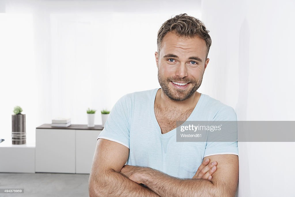 Portrait of young man leaning against wall