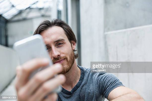 Portrait of young man looking at his smartphone