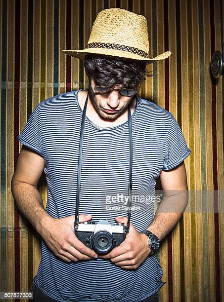 Portrait of young man looking down at vintage camera