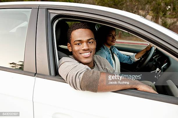 Portrait of young man looking out of car window