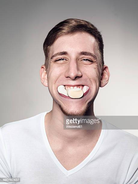 Portrait of Young man mouth suffed with marshmallow and candy