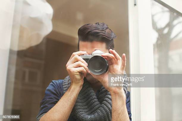 Portrait of young man photographing with SLR camera