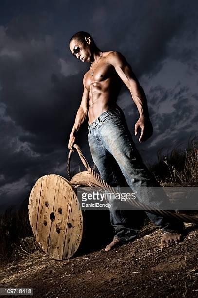 Retrato de jovem homem puxando cabos ao Anoitecer