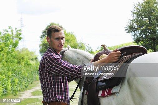 Portrait of young man saddling horse