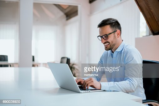 Portrait of young man sitting at his desk in the office : Foto de stock
