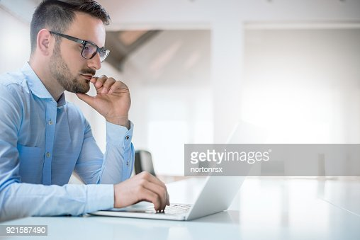 Portrait of young man sitting at his desk in the office : Stock Photo