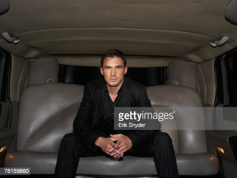 Portrait of young man sitting in  limousine, front view