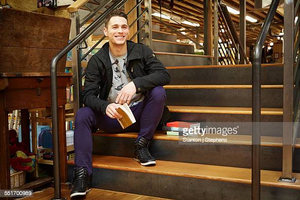 Portrait of young man sitting on book store stairway