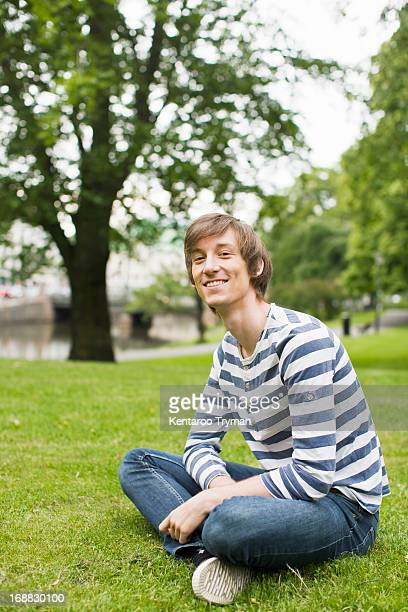 Portrait of young man sitting on grass smiling at park