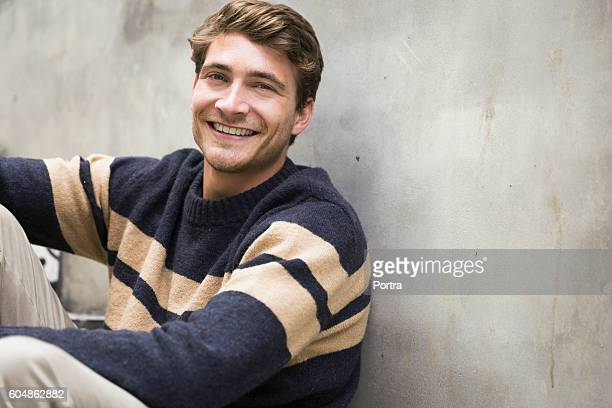 Portrait of young man smiling against wall