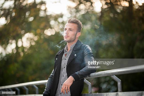 Portrait of young man smoking a cigarette