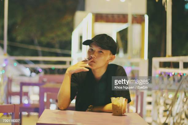 Portrait Of Young Man Smoking At Cafe