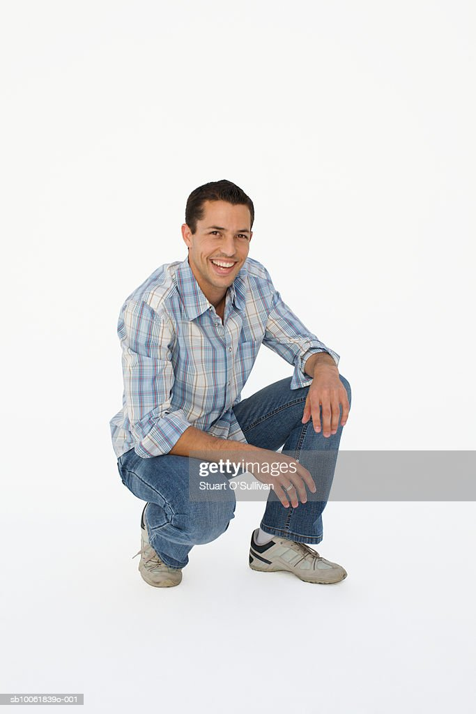 Portrait of young man squatting, smiling : Stock Photo