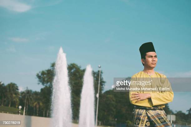 Portrait Of Young Man Standing Against Fountain