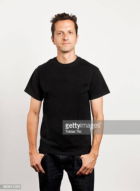 Portrait of young man standing against white background