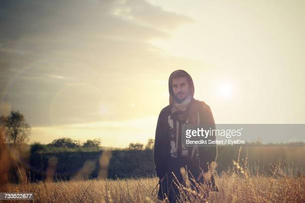 Portrait Of Young Man Standing Amidst Dried Plants On Field Against Sky During Sunset