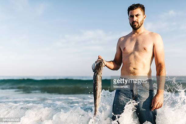 Portrait of young man standing in the water of the sea holding caught fish