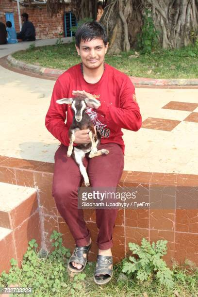 Portrait Of Young Man Stroking Kid Goat While Sitting On Seat
