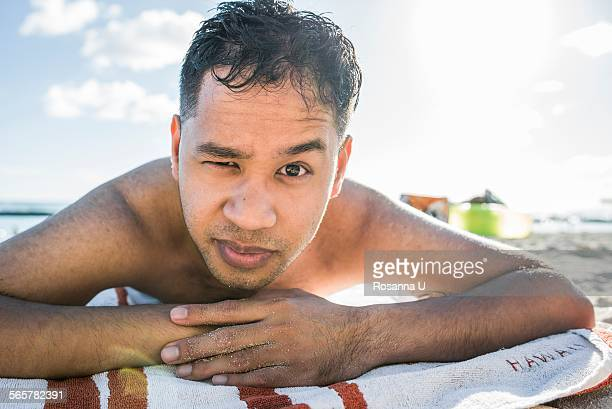 Portrait of young man sunbathing on Waikiki Beach, Hawaii, USA