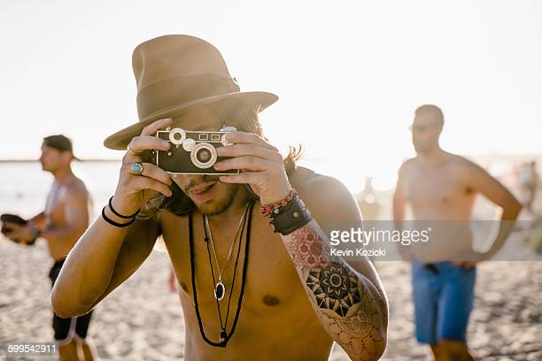 Portrait of young man taking photographs on Newport Beach, California, USA