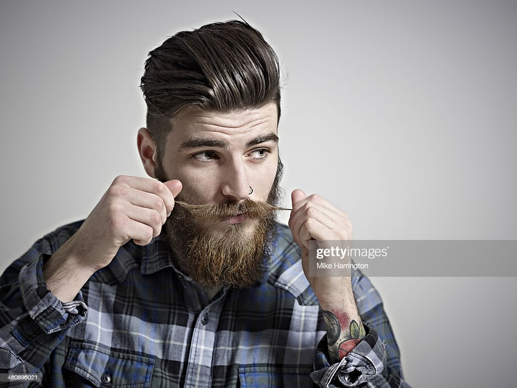 Portrait of young man twisting his moustache. : Stock Photo