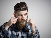 Portrait of young man twisting his moustache.