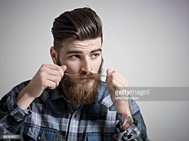 Portrait of young man twisting his moustache.