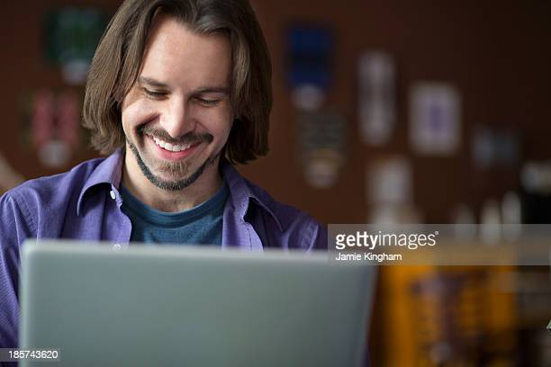 Portrait of young man using at computer in cafe