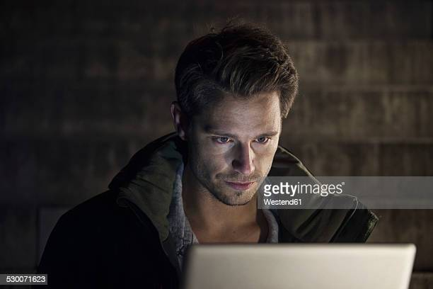 Portrait of young man using laptop at night