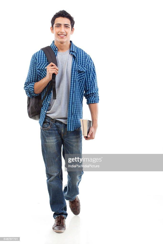 Portrait of young man walking with bag and book over white background : Stock Photo