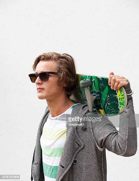 Portrait of young man wearing sunglasses holding skateboard on his shoulders