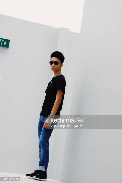 Portrait Of Young Man Wearing Sunglasses Standing By White Wall