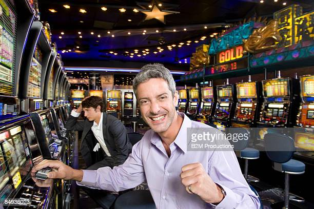 Portrait of young man winning at slot machines